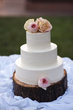 Simple white wedding cake on wooden log cake stand, with real flowers