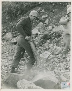 """21 Nov 44. 5/MM-44-30340. Fifth Army, South of Bologna, Italy. Pneumatic hammers are also used as well as sledge hammers, to break rock before it is used for repairing and rebuilding roads washed away by heavy rains. This soldier of the 19th Engineers of the Fifth Army is using the hammer on some of the heavier rock. Photo by Mason. 3131 Signal Service Co."""" South of Bologna, Italy. 21 November 1944"""