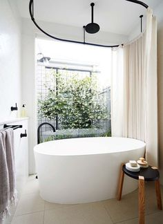 White simple bathtub with simple black faucet outside the tub. Glass window with tree outside, courtyard. Sneak Peek | Inside Out Magazine - July Issue | Poppytalk | Bloglovin'
