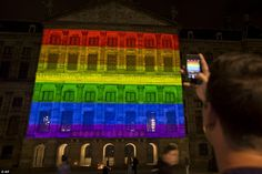 Amsterdam's Royal Palace is lit in the colors of the rainbow flag. The hashtag #LoveWins, ...