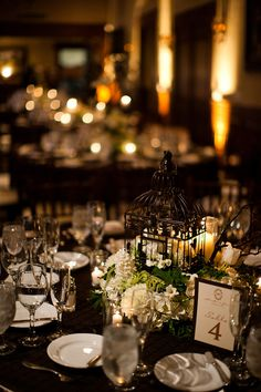 Navy/Black tablecloth, white candles, black birdcage lantern with white and green floral arrangement as centerpiece