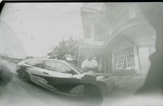 I took this picture with my diy pinhole camera. my brother is standing beside the car.