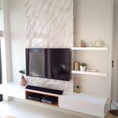 Tv feature wall with a single panel marble backdrop and white finish console