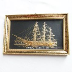 Vintage collage of Cutty Sark by Adam Sheridan is composed of gold watch parts against a black and gold background. Framed wall hanging.