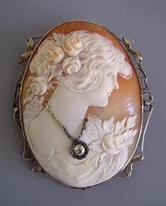 CAMEO  set in white gold filigree. This beautifully carved lady with roses in her hair and on her shoulder also wears a diamond necklace, circa 1900.