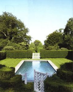 Lap pool surrounded by manicured boxwood hedges for privacy with white chippendale gates