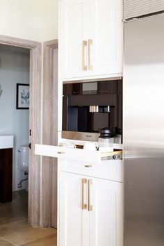 Built-in Miel coffee machine is displayed on a pull out tray between white shaker cabinets accented with brass vertical hardware pulls.