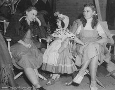 Judy Garland relaxes on the set with Munchkin Olga Nardone and Judy's stand-in Bobbie Koshay.