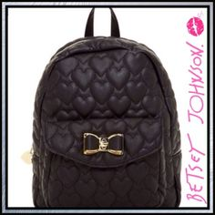 """Betsy Johnson Hearts Betsy Johnson  - Medium Backpack  Details: - Single top back handle - Dual adjustable back straps - Zip-around closure - Heart quilted construction - Exterior features front pocket with bow detail turn-lock flap closure - Interior features wall zip pocket and 2 slip pockets - Approx. 12"""" H x 11"""" W x 6"""" D - Approx. 3.75"""" handle drop, 7.5-16"""" strap drop  Materials: PU exterior, polyester lining Betsey Johnson Bags Backpacks"""