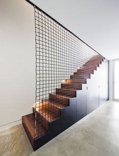 These black and wood stairs with built-in storage, and a wire mesh net, that is not only visually interesting, it also acts as a safety barrier.
