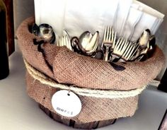 """old bushel basket and lined it with part of a coffee sack. I tied a piece of rope around the overhang and attached this cute little merci clay tag to it. Then filled it with our white cloth napkins and all the beautiful vintage flatware """"bouquets."""