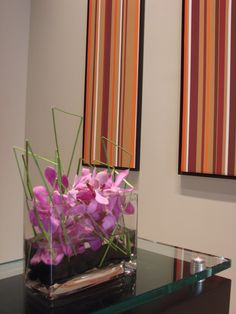 This is a floral arrangement that features pink mokara orchids with blades of grass.