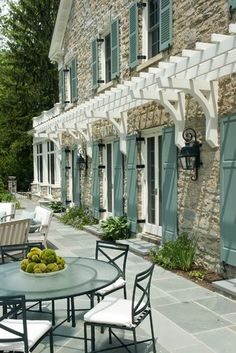 small white pergola attached to stone house with light blue shutters and outdoor glass table and chairs on slate bluestone patio Exterior Color Schemes, Exterior House Colors, Exterior Paint, Exterior Design, Interior And Exterior, Exterior Shutters, Stone Exterior, Stone Facade, Painting Shutters