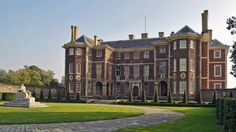 The front elevation of Ham House, Surrey, taken from the right and showing the seeping circular drive and a glimpse of the river god statue ...