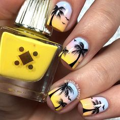 Pretty Palm Tree Nail Art design. The skies are painted in soft morning colors with hints of yellow. The palm trees and the birds are seen in silhouette styles overlooking the beach.