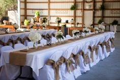A nice idea for head table with the burlap runner if we have to have a white table cloth. Also the burlap bows on chairs is nice