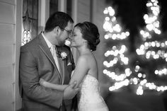 Gorgeous winter wedding photo with the light of the Christmas trees behind them