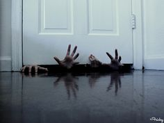 Hands Under The Door. Add a pool of fake blood seeping out from under the door for extra creepy points.