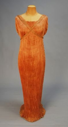 """TRAINED FORTUNY DELPHOS GOWN with ORIGINAL BOX, c. 1920. Pale orange silk having draw- string neckline, side seams decorated with brown striped yellow beads, stenciled bodice bands (detached), tape label """"Fortuny Depose Made in Italy"""", drum shaped box with Madison Avenue boutique label on lid, Fortuny store label with customer name and address on bottom. Bust 38, front length 55, back length 63. (Small spot on front, draw- string frayed, stitch marks from bands) good"""