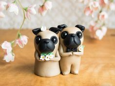 This keepsake Pug Wedding Cake Topper features two fawn Pugs. They have tiny paws and tails that curl into spirals and they are adorned with