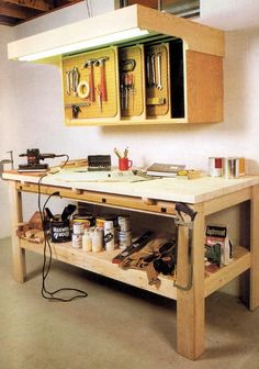 Cabinet with multiple sliding doors and an incorporated light that extends over the work table/bench.