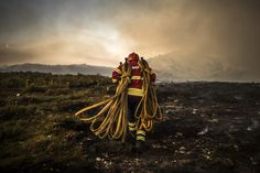 Forest fire in Vila do Soajo. Mit Löschschläuchen ausgerüstet zum Einsatz. Ein Feuerwehrmann auf dem Weg zur Arbeit im Waldbrandgebiet im Norden Portugals.