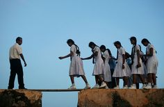 10 Most Incredible,Unusual and Dangerous Journeys To School In the World:  School girls walking across a plank on the wall of the 16th century Galle Fort in Sri Lanka
