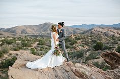 Vasquez rocks wedding photo shoot bride lace style gown with high neckline and red and orange floral headpiece and groom grey suit with white dress shirt and tan stripped bow tie with rose boutonniere