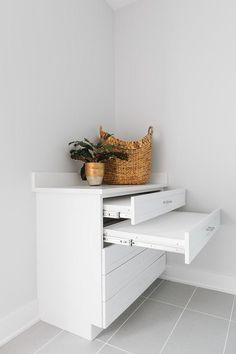 Gray grid tiles are fitted beneath a drawers that conceal pull out drying racks. Small Laundry Space, Laundry Room, Drying Racks, Mudroom, Houston, Grid, Tiles, Drawers, Room Tiles