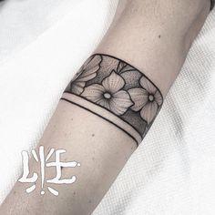 Tatouage tour d'avant bras, bandeau floral et ligne, noir.
