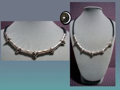 Collar de calaveras de y tubos forma de hueso en zinc con entrepiezas plateadas cordón de caucho negro