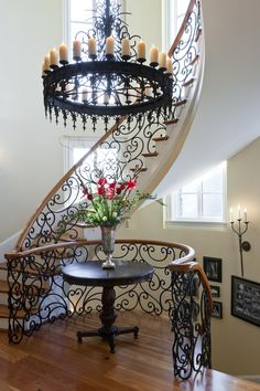 We love this chandelier and staircase design! The wrought iron tied in with the wood is beautiful! This room, interior design, and decor boasts elegance!