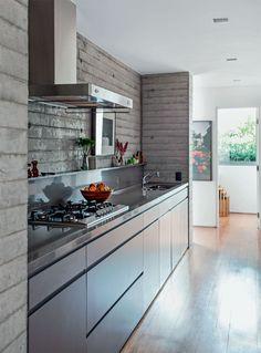 A caixa de concreto moldado setoriza a cozinha, exibindo a marca das fôrmas de madeira empregadas na obra. Projeto SAO Arquitetura.