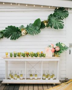 This is a nice option if you want to go a little more elegant with the table designs.  A simple tropical floral arrangement and palm leaves.