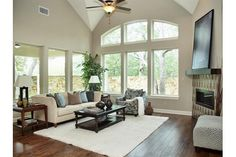 Soaring windows offer a view of a stone wall and trees from this great room. The Rosslynn plan built by David Weekley Homes in Wynn Ridge Estates. McKinney, TX.
