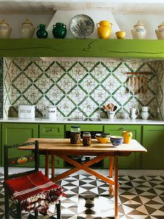 Love the kitchen tiles on backsplash and floor. Great take on Manhattan style   I'm not sure though if I'd grow tired of the color. But I LOVE LOVE LOVE the crockery on the upper shelf.