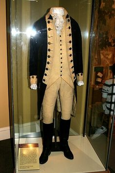 This blue wool coat is part of a suit of regimentals made for George Washington in 1789. It has a buff wool rise and fall collar, buff cuffs and lapels, and buff lining; there is a row of yellow metal buttons on each lapel, as well as on each cuff