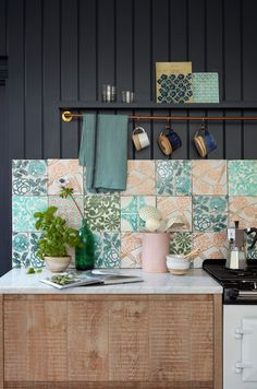 Create beauty in utility with a floral motif splashback. Different patterns in harmonious colours bring a pleasing informality. Dark walls create contrast and allow the designs to stand out. Kitchen On A Budget, Diy Kitchen, Kitchen Interior, Kitchen Decor, Beautiful Wall, Beautiful Homes, House Beautiful, Kitchen Splashback Tiles, Kitchen Soffit