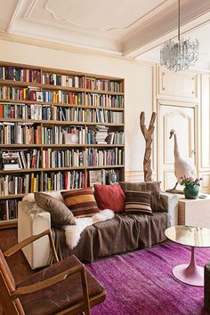I spy some swan taxidermy. Unless it's a pet?  Purple area rug, saarinen style tulip table, wall of books.