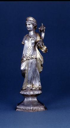 Silver statuette of the goddess Fortuna, probably a used as a table decoration. Date 200-225 (circa). From Gaul.   Silver statuette of the goddess crowned, with gilt traces; she holds a cornucopia in her left hand, her right arm is lost. Roman, 200-225 CE. London, British Museum.