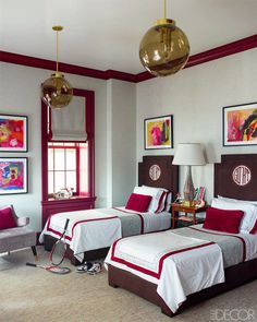 A boys' bedroom features Danish pendant lights and headboards with custom monograms by Leontine Linens; the wallpaper is by Phillip Jeffries, the window frame is painted in Pratt & Lambert's Garnet, and the carpet is by Stark.