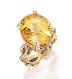 18 KARAT GOLD, YELLOW SAPPHIRE, PINK SAPPHIRE AND DIAMOND RING The oval-shaped yellow sapphire weighing approximately 10.50 carats, within a mounting of wave design set with small round diamonds weighing approximately 1.40 carats, decorated with round pink sapphires, size 5½, signed Wendy Brigode.