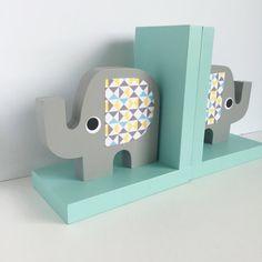 Estos hechos a mano, elefante sujetalibros agregará un toque hermoso al espacio de su hijo mientras que mantiene sus libros favoritos organizados. Color: Elefantes de gris con luz verde azulado sujetalibros base. BASE DE SUJETALIBROS: Usted elige: -Azul borde solamente -Toda Base