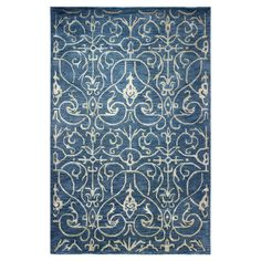 Add a pop of pattern to your living room or den with this hand-tufted wool and art silk rug, showcasing a scrollwork motif for stylish appeal.