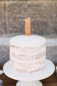 """Trendy """"naked"""" cakes like this one are gorgeous for weddings but are even better for moms looking to cut back on the sugar so often found at parties. And for a 1st birthday party - it's even more perfect since it's likely it's the very first time the birthday boy or girl will be sampling cake or large amounts of sugar in one sitting."""