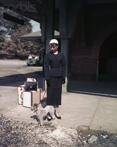 "The actress Audrey Hepburn (as Sabrina Fairchild, with the Poodle called ""David"") photographed at the train station of Glen Cove, a city in Nassau County (a suburban county on Long Island), in the state of New York (USA), during the filming of her new movie ""Sabrina"", in October 1953."