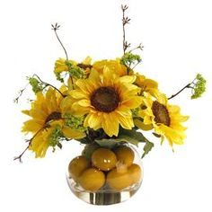 "I actually really love this idea for an arrangement.  Put the sunflowers in a small jar with water, then put in a larger vase and arrange lemons around it to hide the small jar.  Silk sunflower and lemon arrangement in a glass vase.   Product: Faux floral arrangementConstruction Material: Silk, plastic, and glassColor: Yellow and greenDimensions: 12"" H x 12"" Diameter"