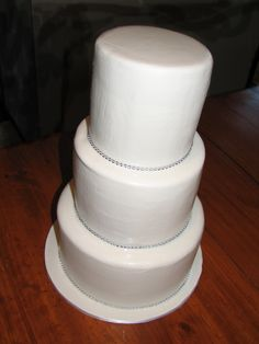 White chocolate mudcake. Double height three tier cake with white fondant and diamontes. Check out my page at www.facebook.com/cakesbyleannerhodes