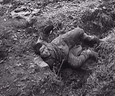 Terrified Red Army POW pleads for his life as he is about to be shot by the Waffen SS. His comrade in the top right of the photo, covered with tree branches, has already been shot.