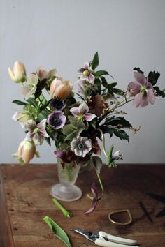 Anemones, helleborus, pale tulips arrangement in a vase - mauve and ivory, an image like an old painting